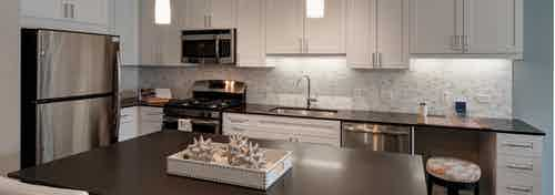 AMLI Deerfield apartment kitchen with dark countertops and white cabinets with stainless steel appliances and an island