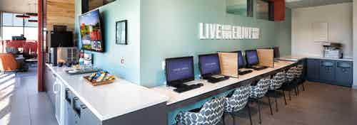 Tech lounge at AMLI on Aldrich with desktop computers at a long white desk against a light teal wall with patterned chairs