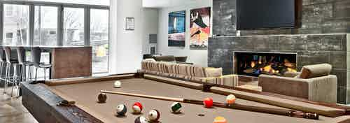 AMLI Mark24 clubroom with billiards table in foreground with cue and balls and cozy seating and big screen TV by fireplace
