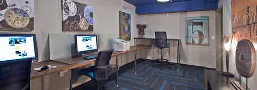 Interior of the business center at AMLI 535 apartments with computers a printer and seating area with colorful floors white walls and blue ceiling
