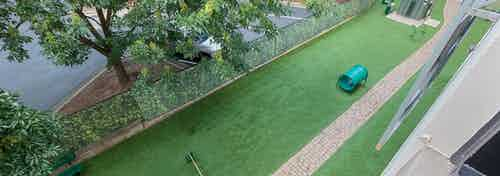 Overhead view of grassy outdoor paw park at AMLI Ponce Park apartments with small tunnels for dogs to jump through