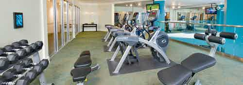 Alternate angle of AMLI North Point fitness center with a dumbbell rack and bench across a line of exercise machines