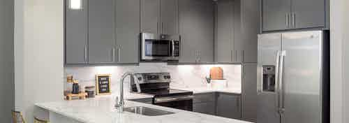 AMLI Addison kitchen with grey wood cabinets and white countertops with matching backsplash and stainless steel appliances