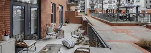 AMLI Downtown oversized poolside resident patio with brown wicker furniture and gray cement flooring beside red brick building