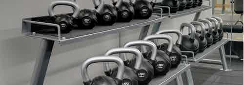 Interior view of the fitness center at AMLI Evanston apartment community with kettlebell weights lined up on stacked shelves