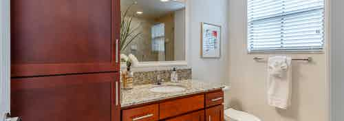 Interior view of AMLI Toscana Place apartment bathroom with wood vanity and granite counter with mirror above and side window