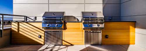 Daytime view of outdoor rooftop lounge with two stainless steel barbecue stations at AMLI Littleton Village apartments