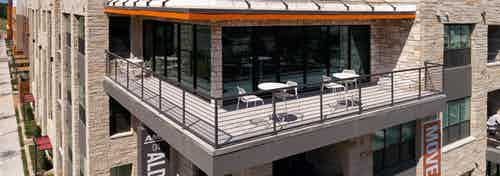 Exterior daytime view of rooftop balcony at AMLI on Aldrich apartment community with outdoor tables and chairs