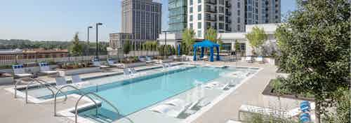 Daytime view of the pool at AMLI 3464 with surrounding white lounge chairs and a royal blue canopy in the background