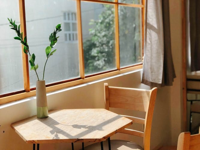 Sunlight flowing through a window onto a small wooden table