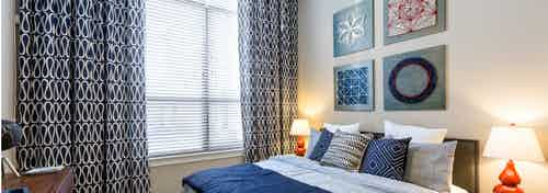 AMLI on Riverside bedroom with blue and grey bed against a creme wall with a large window with patterned curtains to the left
