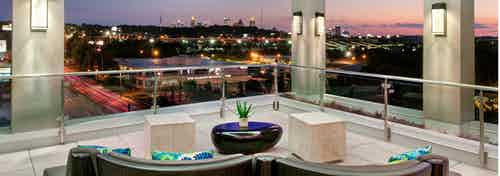 Nighttime exterior shot of AMLI Piedmont Heights sky deck with various couch seating to overlook lit up Atlanta skyline