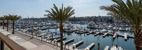 Daytime view of the walking promenade, marina and boat slips from an elevated lounge deck at AMLI Marina Del Rey apartments