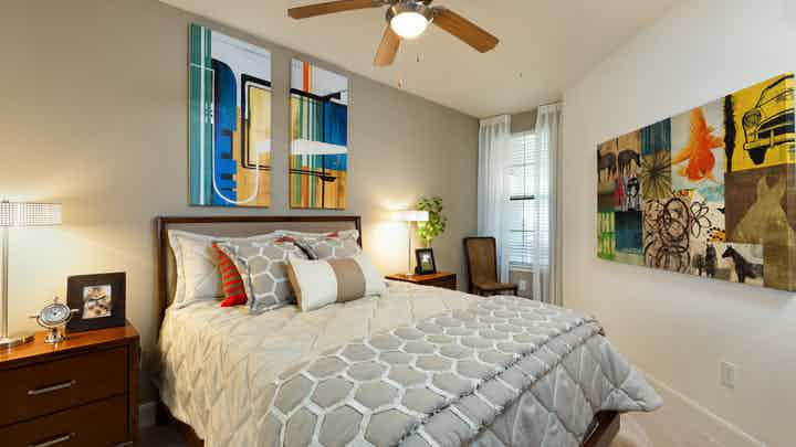 Interior view of AMLI 2121 apartment bedroom with light green wall, bed, nightstands, lamps and window with curtains