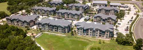 Daytime aerial view of AMLI Covered Bridge apartment community complex, surrounding green grass lawns, and parking