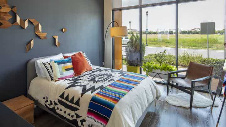 AMLI on Aldrich apartment bedroom with colorful bed on dark gray wall and floor to ceiling windows with view of green field