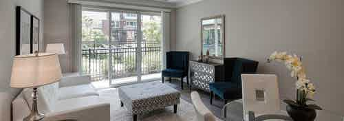 Interior of AMLI Deerfield apartment dining room and living room with private balcony overlooking courtyard pool view