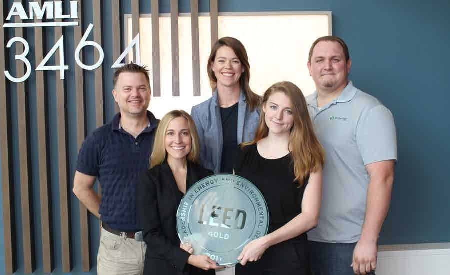 The AMLI 3464 team posing with their LEED Gold award in the lobby of the apartment community
