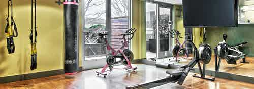 AMLI Mark24 yoga studio with yellow TRX straps and punching bag and spin bike and row maching and TV for fitness on demand