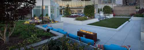 AMLI Arts Center rooftop firepit with a straight line of blue couches behind it and surrounding green landscaping