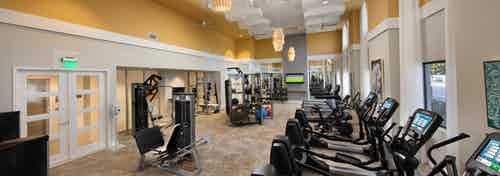 Interior of the fitness center at AMLI 8800 with treadmills, weight machines, yoga balls and vibrant yellow walls