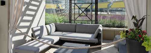 Alternate view of the cabana at AMLI River North with an L shaped couch and a bright potted plant with white curtains