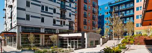 Exterior entrance to AMLI Mark24 white blue and orange building with patios and trees bushes and view of the sidewalk