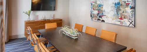 A conference room at AMLI Denargo Market apartments with a long table and chairs and a large piece of art and television