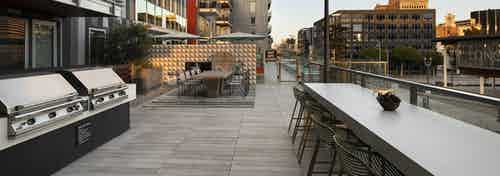 Dusk view of AMLI Park Broadway apartment building rooftop lounge with two long tables and chairs and two barbecue grills