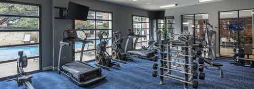 Day view of AMLI Eastside poolside fitness center with a cardio and strength training machines and TVs set on blue carpet