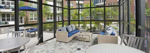 Interior view of the screened pool cabana at AMLI Decatur on a sunny day with sofa and blue pillows and white tables