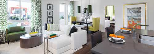Interior of AMLI Lex on Orange furnished apartment living room with white couch and dining table in front of large windows