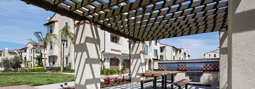 Daytime view of AMLI Spanish Hills apartment building wood pergola with grill station, picnic table and lush landscaping