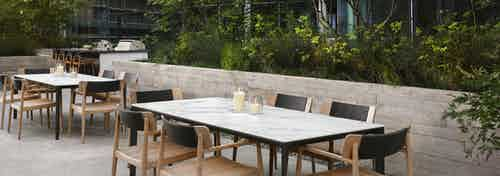 AMLI Fountain Place outdoor dining area with two white marble top tables with chairs and lush green trees and hanging lights