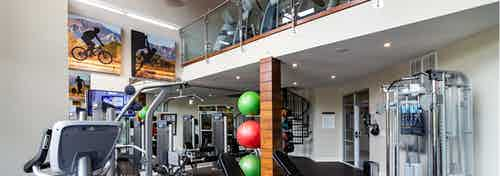 View of two story fitness center at AMLI Riverfront Park apartments with free weights and other strength training machines