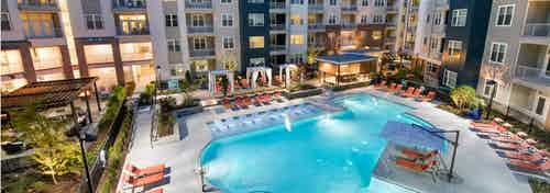 Angle of AMLI Buckhead pool facing the building exterior with surrounding orange lounge chairs on the pavement