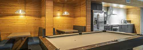 Interior view of clubroom AMLI Mark24 with booth seating and billiards table and kitchen with stainless steel appliances