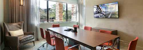 Interior view of AMLI Covered Bridge resident conference room with an eight-person table and a large screen monitor