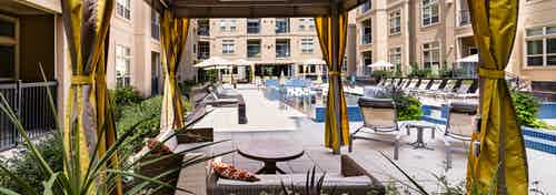 Daytime view of AMLI RidgeGate apartments landscaped pool deck from personal curtained cabana with plentiful lounge seating
