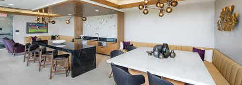 Interior of sky lounge deck at AMLI Decatur apartment building with serving kitchen and large TV with booth seating areas
