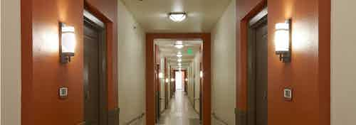 Interior view of hallway at AMLI on Riverside with light walls and modern light fixtures next to each apartment door