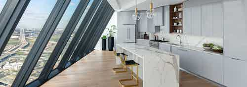 Kitchen with white stone island and gray cabinets and floor to ceiling sloped windows at AMLI Fountain Place apartments