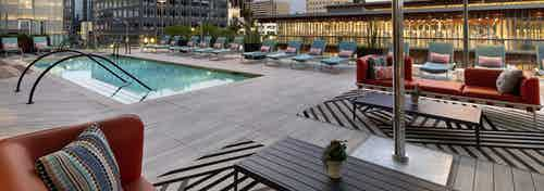 Dusk view of AMLI Park Broadway pool deck with colorful lounge and couch seating and umbrellas overlooking the city