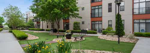 AMLI Old 4th Ward outside courtyard with luscious green grass and tulips with benches to sit on to breathe in fresh air