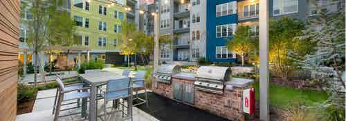 Outdoor grilling area at AMLI Piedmont Heights with stainless steel grill and counter space for food prep with high top table