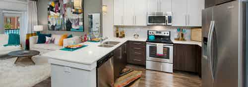 Interior of AMLI Piedmont Heights kitchen with stainless steel appliances and white granite countertops with dark hardwood
