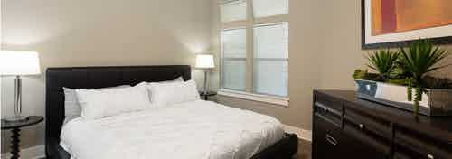 Close up of AMLI 5350 bedroom with black bed frame and white bedding near a tall window with modern lamps on either side