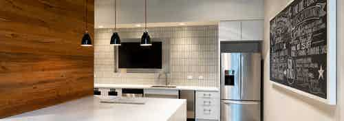 Interior of resident serving kitchen at AMLI Frisco Crossing apartment building with stainless steel appliances and big screen TV