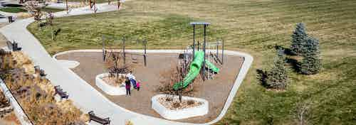 Daytime aerial view of a family at a children's playground in park adjacent to AMLI Littleton Village apartment building