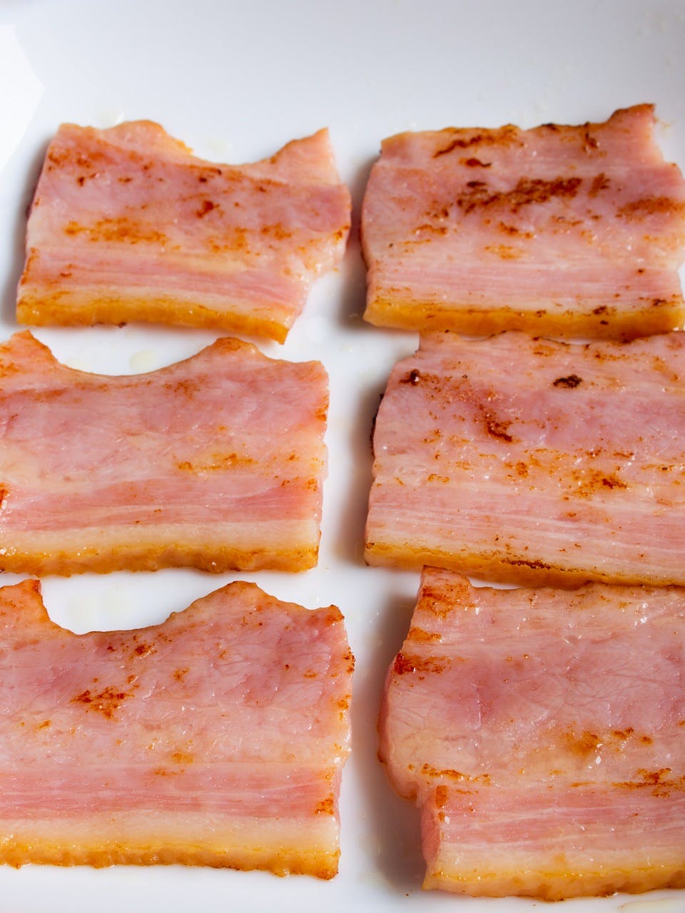 six cooked squares of bacon  on a white plate
